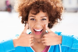 Woman smiling and giving the thumbs up