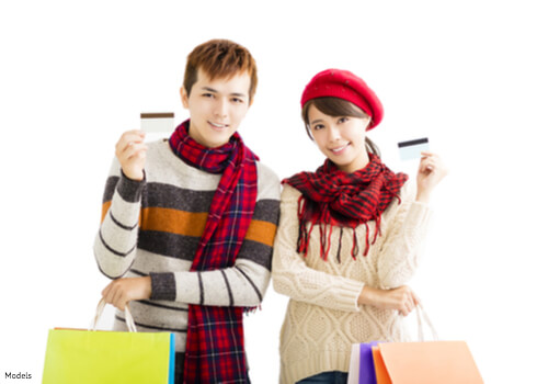 Man and woman holding gift cards and shopping bags