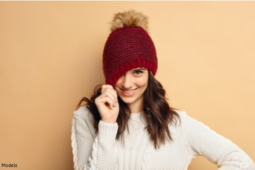 Woman pulling hat over one eye and smiling