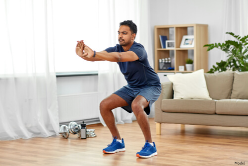 Man performing a squat in his house