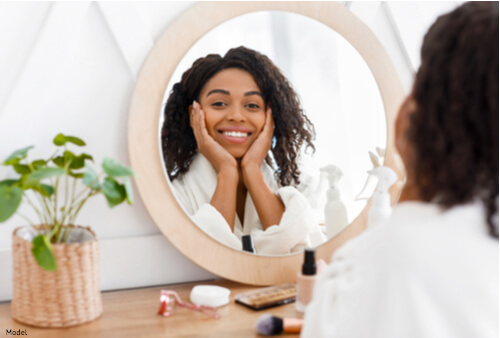 Woman looking her smooth skin in the mirror